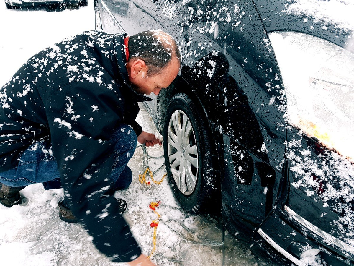 Putting on snow chains is a reality when driving in Austria in winter.